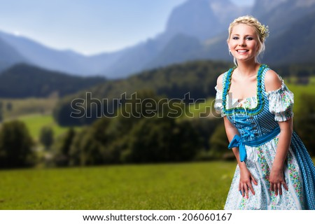 attractive young woman in a dirndl with alps background - stock photo