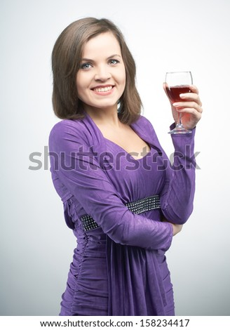 Attractive young woman in a lilac dress. Holding a glass of wine. On a gray background - stock photo