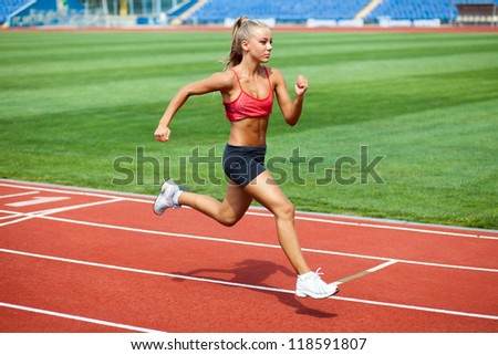 Attractive young woman in a sports suit running on a treadmill at the stadium - stock photo