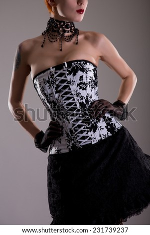 Attractive young woman in black and white corset with floral pattern, studio shot    - stock photo