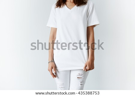 Attractive young woman in blank white T-shirt with copy space for your text or advertising content. Cropped portrait of pretty Caucasian teenage brunette girl posing against white concrete wall - stock photo