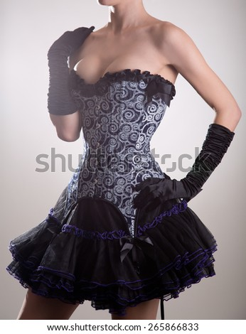 Attractive young woman in blue corset and black skirt, studio shot  - stock photo