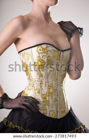 Attractive young woman in burlesque corset and skirt, studio shot on white background  - stock photo