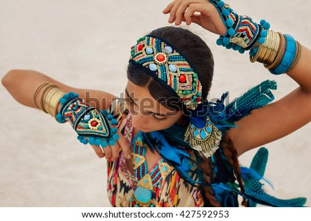 attractive young woman in ethnic jewelry outdoors - stock photo