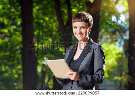 Attractive young woman in formal wear holding digital tablet and smiling looking at camera while standing outdoors - stock photo