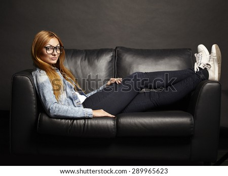 Attractive young woman in glasses sitting on black sofa on black background - stock photo
