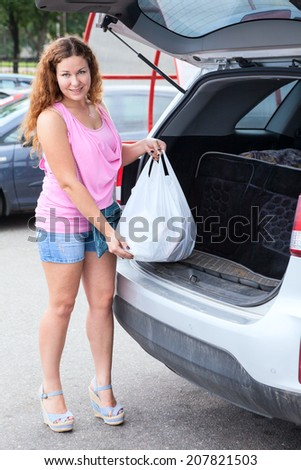 Attractive young woman in pink clothes loading bag in suv - stock photo