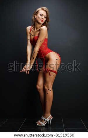 Attractive young woman in red lingerie on dark background - stock photo