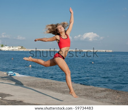 Attractive young woman in red sportswear jumping on the background of the sea - stock photo