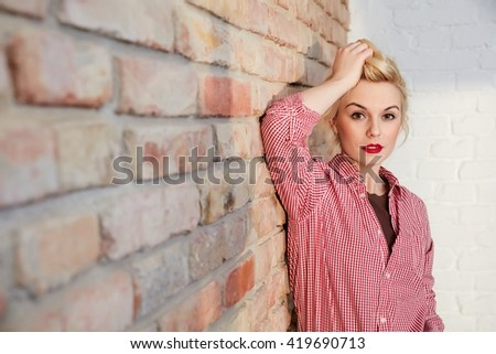 Attractive young woman in retro style posing hand in hair over brick wall. - stock photo