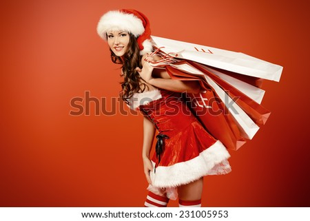 Attractive young woman in Santa Claus costume holds shopping bags over red background. Christmas. - stock photo