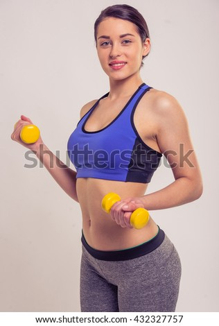 Attractive young woman in sportswear is holding dumbbells, looking at camera and smiling, on a gray background - stock photo