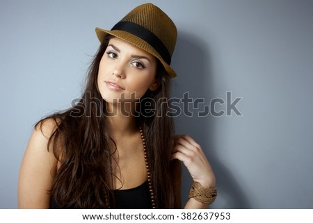 Attractive young woman in straw hat with long hair, looking at camera. - stock photo