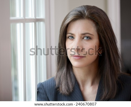 Attractive young woman in suit looking at camera - stock photo