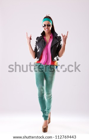 Attractive young woman in sunglasses high heels and casual clothes making the rock and roll hands gesture - stock photo
