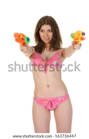 Attractive young woman in the pink bikini hold two squirt guns - stock photo