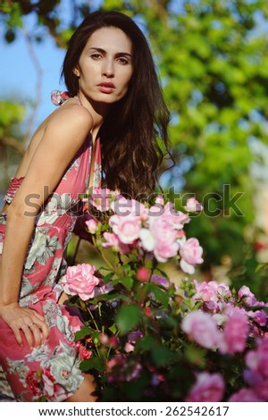 Attractive young woman in the rose garden - stock photo