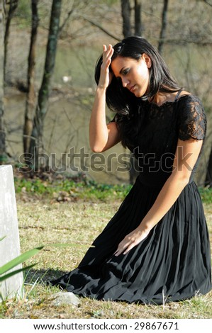 Attractive young woman in vintage black dress next to head stone - stock photo