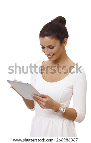Attractive young woman in white dress using tablet computer, smiling happy. - stock photo