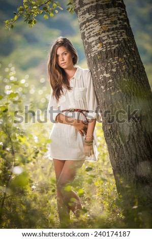 Attractive young woman in white short dress posing near a tree in a sunny summer day. Beautiful girl enjoying the nature in a green forest. Portrait of sensual female in white daydreaming in a meadow - stock photo