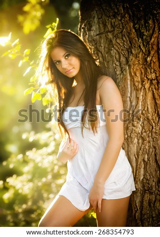 Attractive young woman in white short dress posing near a tree in a sunny summer day. Beautiful girl enjoying the nature in a green forest. Portrait of sensual female in white posing in a meadow - stock photo