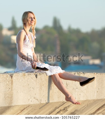 Attractive young woman in white sundress puts on shoes on open air. Girl with pigtails puts on shoes looks away smiling - stock photo
