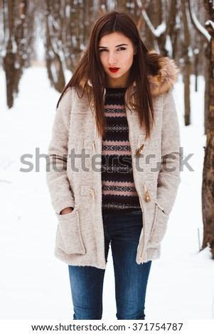 Attractive young woman in wintertime outdoor.  Girl in a winter coat and mittens walks in the winter woods. Portrait of brunette with framed lips. - stock photo