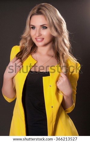 Attractive young woman in yellow jacket - stock photo