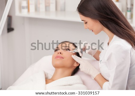Attractive young woman is getting a collage injection in her face. She is sitting calmly at clinic. The expert beautician is filling female nasolabial wrinkles by hyaluronic acid and smiling - stock photo