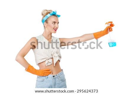 Attractive young woman is stretching her hand with cleaning spray aside. She is smiling and looking at it with interest. The girl is wearing rubber gloves. Isolated on background - stock photo