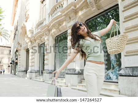 Attractive young woman joyfully walking down a shopping street in a classic city, holding shopping bags up with her arms and smiling at the camera. - stock photo