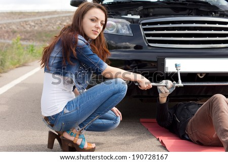Attractive young woman kneeling in front of her broken down car handing a spanner to a mechanic working underneath the engine compartment - stock photo