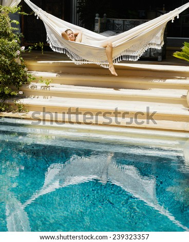 Attractive young woman laying down and relaxing on a white hammock while on vacation in a tropical garden - stock photo