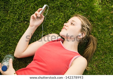 Attractive young woman laying down on a park green grass, taking a break from exercising while listening to music with her mp4 player and earphones. - stock photo