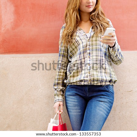 Attractive young woman leaning on a colorful orange city wall using a high tech smartphone and carrying shopping bags, smiling. - stock photo