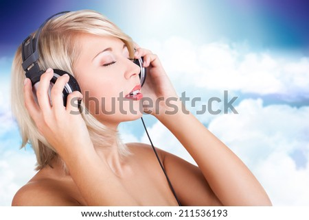 attractive young woman listening to music - stock photo