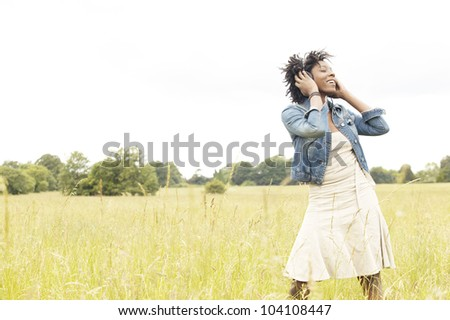 Attractive young woman listening to music with headphones in an open field, dancing and singing. - stock photo
