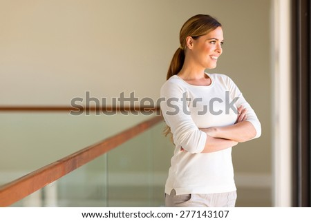 attractive young woman looking outside window - stock photo