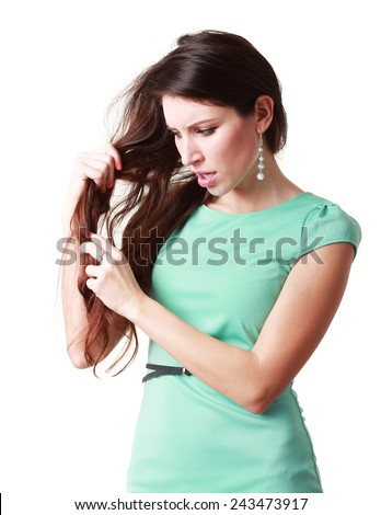 Attractive young woman looking unhappy with the condition her long hair - stock photo