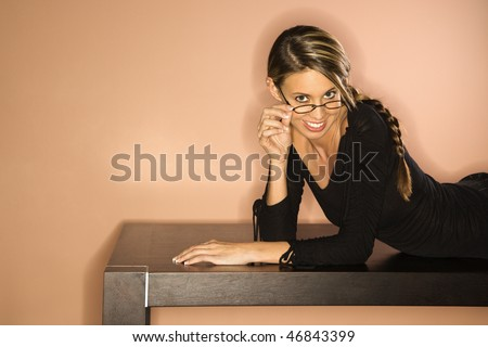 Attractive young woman lying on a table. She is pulling her eyeglasses down over her nose as she looks towards the camera. Horizontal shot - stock photo
