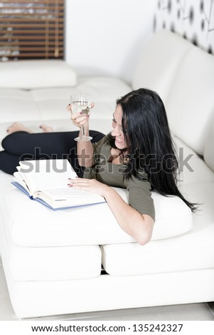 Attractive young woman lying on her sofa enjoying a glass of wine and a good book. - stock photo