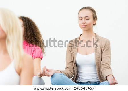 attractive young woman, meditating with closed eyes, group meditation - stock photo