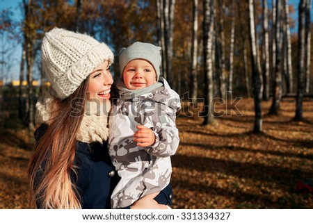 Attractive young woman mother with her son in her arms. Portrait of a happy mother and baby laughing. Young mother holding her baby - stock photo