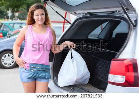 Attractive young woman near own car with shopping bag - stock photo