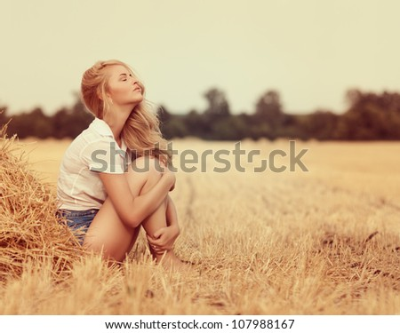 Attractive young woman near the stacks of straw - stock photo