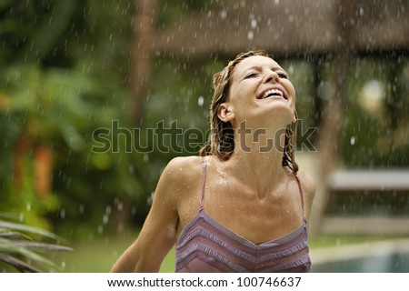 Attractive young woman on holiday under tropical rain, enjoying the shower. - stock photo