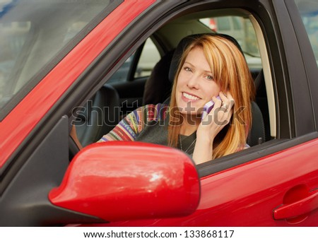 Attractive young woman on phone in car - stock photo