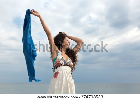 Attractive young woman on the beach waving with a blue scarf - stock photo
