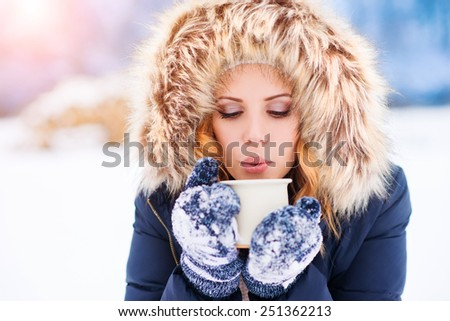 Attractive young woman outside in snow with a cup of coffee - stock photo