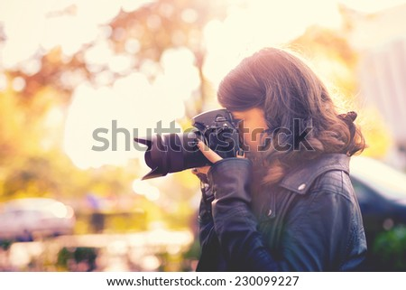 attractive young woman photographer taking pictures with professional digital camera outside. vintage effect - stock photo